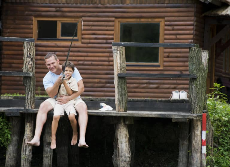 Father and son fishing in front of their wooden cottage on water, shallow doff