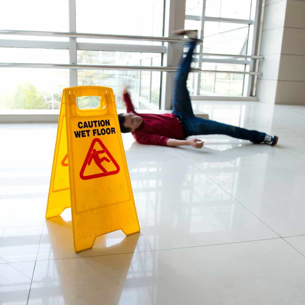 Man slipped on wet floor with wet floor sign nearby