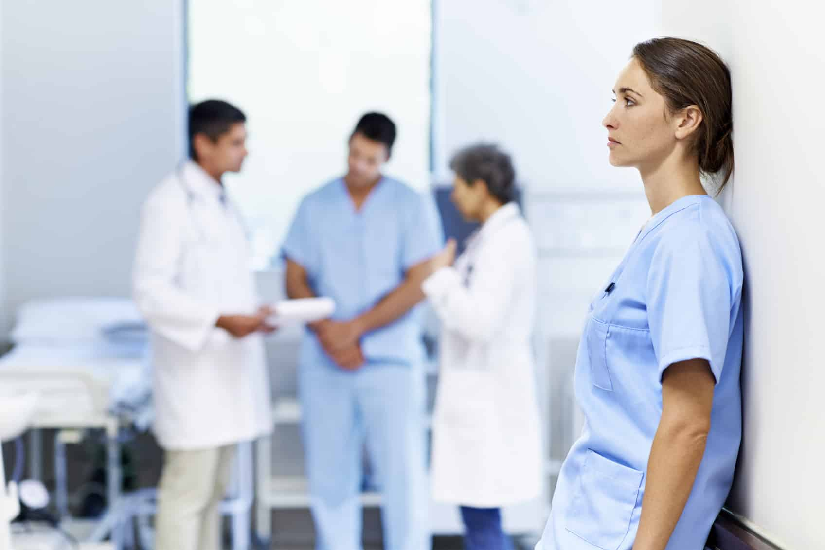 Shot of a tired looking nurse leaning against a wall with colleagues in the background