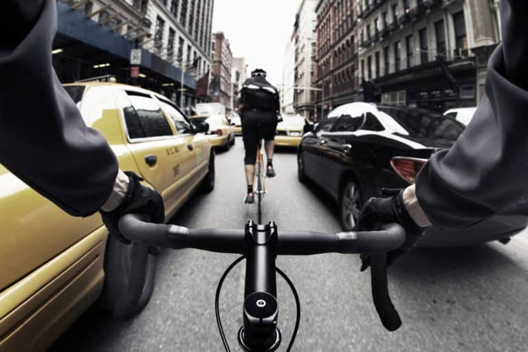 The handlebar view of a male bike courier in New York City.