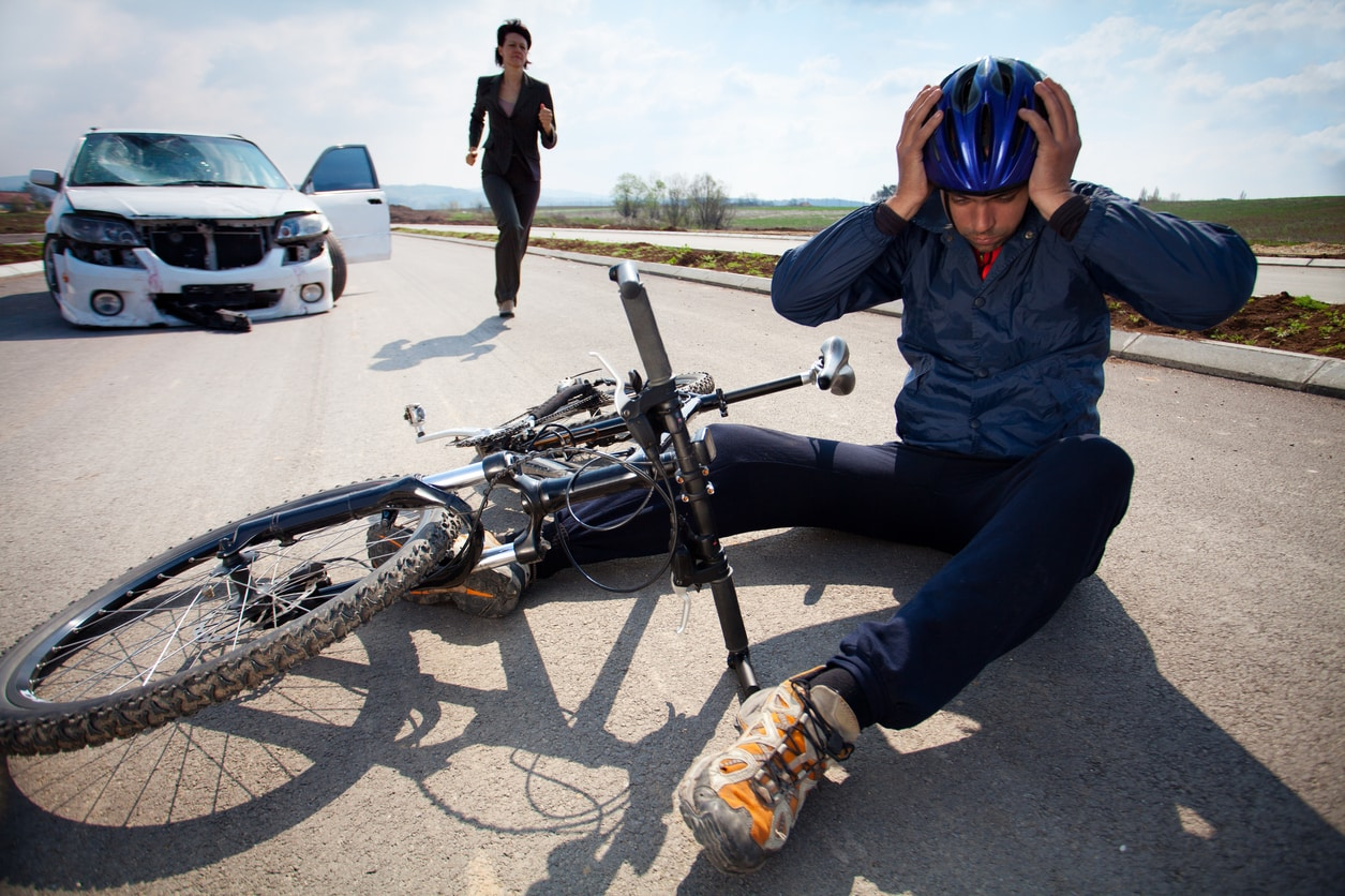 Bicyclists injured in a car accident lying down on the road and holding his head with helmet. A person who is driving car running to helps to injured man.