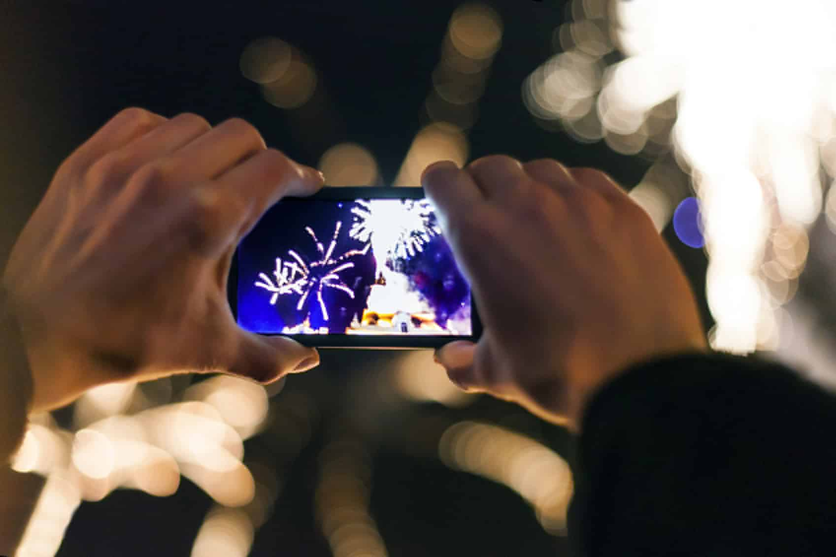 Human Hand Holding phone camera over fireworks
