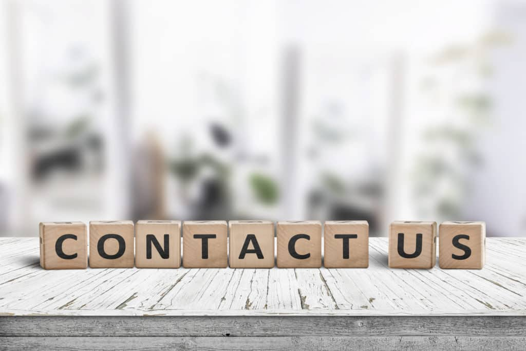 Contact us sign on a wooden desk