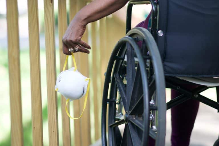 Person in wheelchair holding a mask