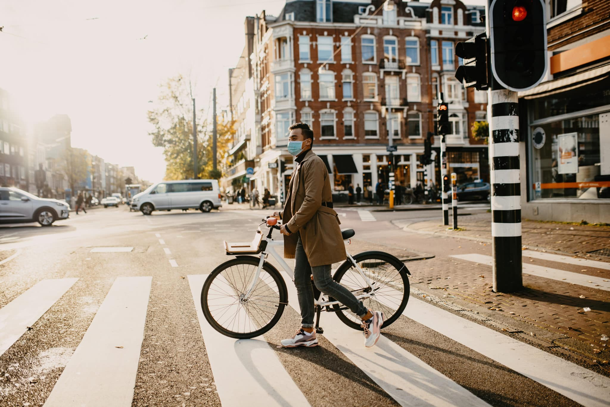 Man with face mask pushing bicycle in the city during coronavirus pandemic lockdown