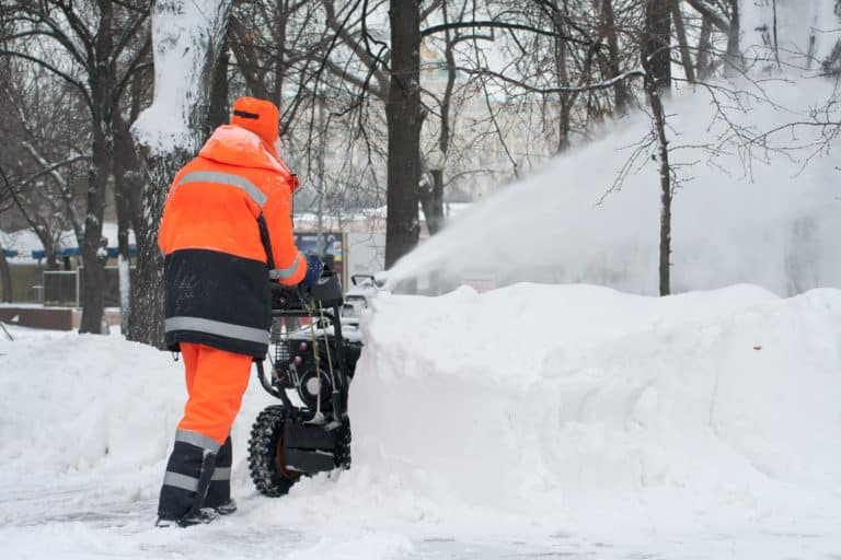 Snow blower being used by person in high vis