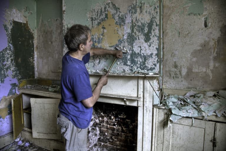 Man scraping old paint and wallpaper off a wall at the start of a house renovation project.