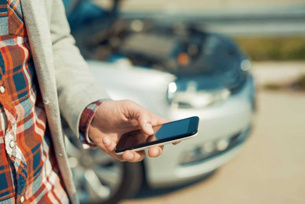 Man using smartphone after traffic accident