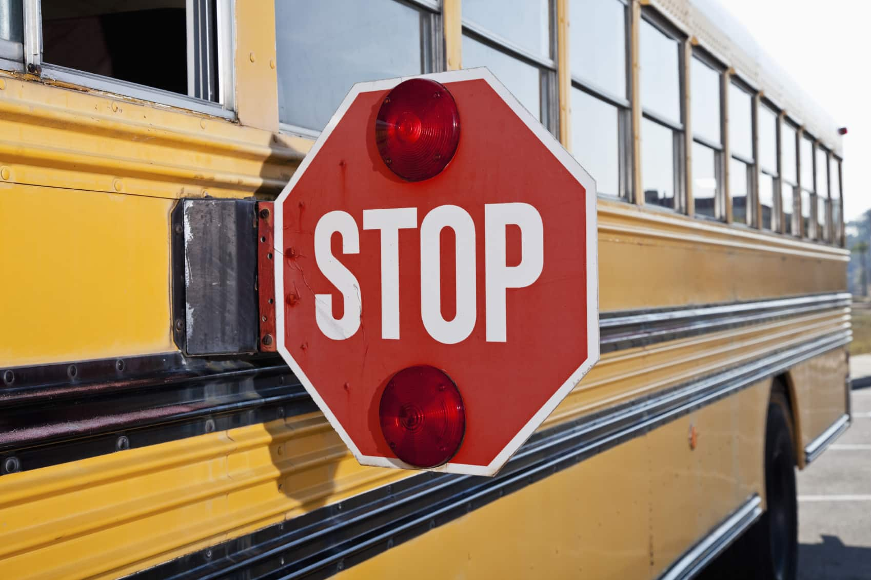 Stop sign on side of yellow school bus.