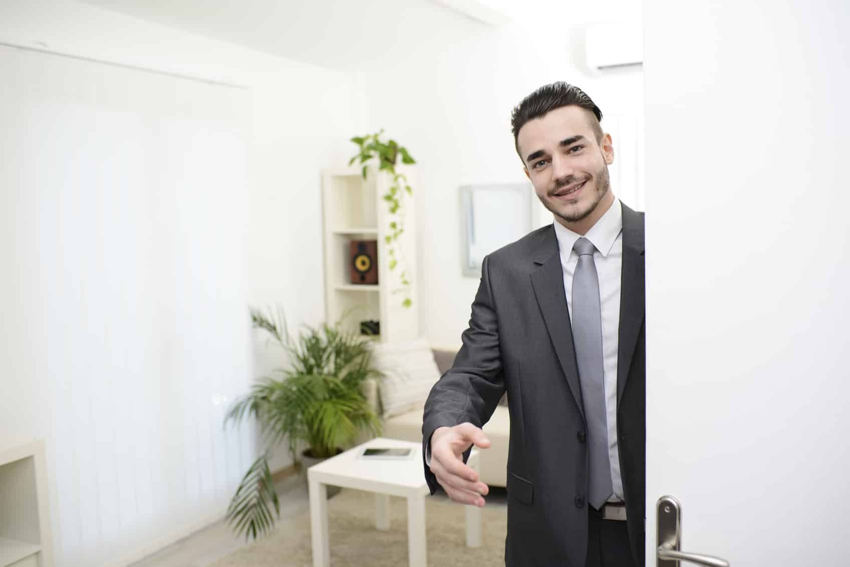 young businessman at doorway giving hand to customer